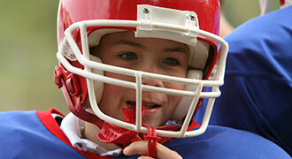 Child with mouthguard playing football