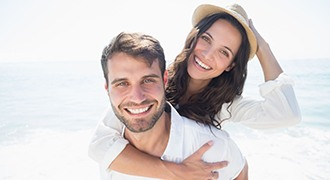 young couple smiling on beach with veneers in Tyler