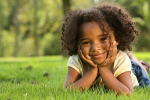 young girl curly hair smiling