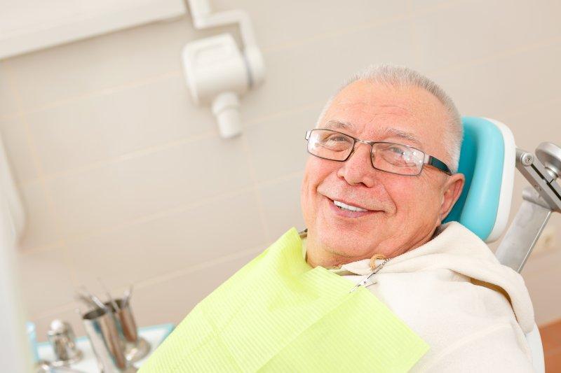 older man smiling in dentist chair